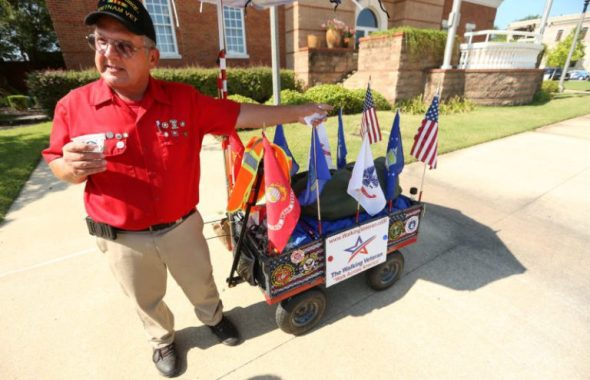 Adam Robison | BUY AT PHOTOS.DJOURNAL.COM Thomas Wayne Hudson, the walking veteran, walks with Tupelo Mayor Jason Shelton about pulling his cart in front of City Hall Monday morning in Tupelo.